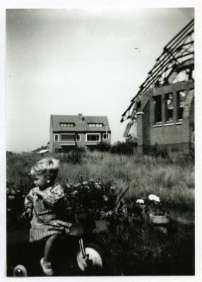 Kleuter op driewieler bij vernielde Sint-Barbarakerk, 1944